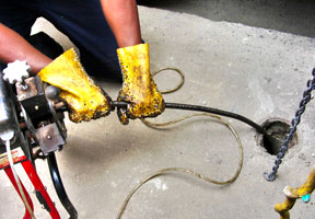 plumber performing drain cleaning on the main drain of a residential property