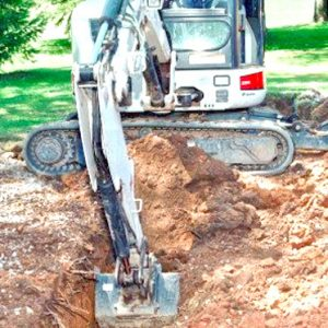 A digging machine upearths the ground infront of a Toronto home
