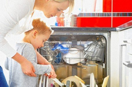 woman standing next to newly installed dishwasher with son