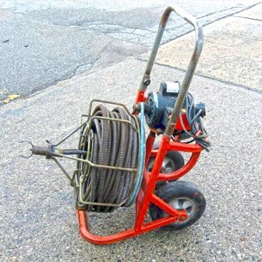 drain snake machine sitting on the sidewalk after being rented