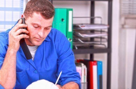 plumbing contractor answering telephone