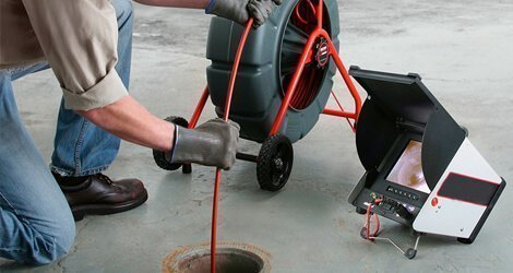 Plumber executing a drain inspection using a drain camera