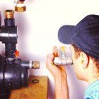 man installing a pump to help reduce moisture in basement