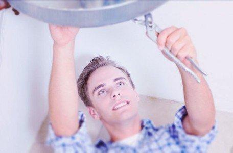 repair man fixing hot water heater