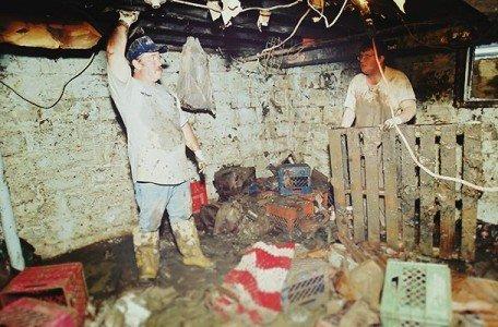 men assessing damage to flooded basement