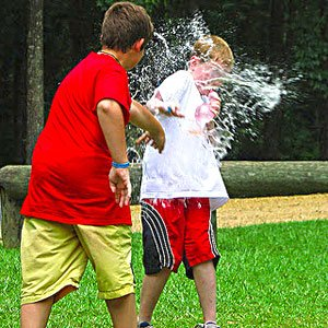 kid throwing a water balloon at another kid