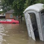 flooding in Windsor, ON showing a car in the water and an outhouse tipping over