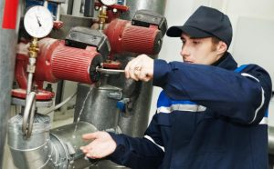 Commercial plumber inspecting valve assembly