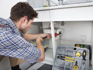Brampton plumber repairing drain beneath sink