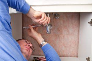 A Burlington plumber repairing a sink drain