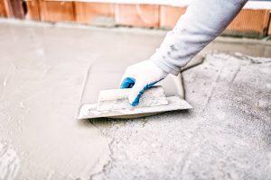 Georgetown plumber using trowel during basement waterproofing