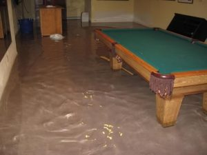 a flooded room in a basement, water is clearly visible on the floor at near ankle height