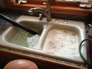a kitchen sink filled to the brim with soapy water, a drain cleaning device is visible attempting to remove the blockage