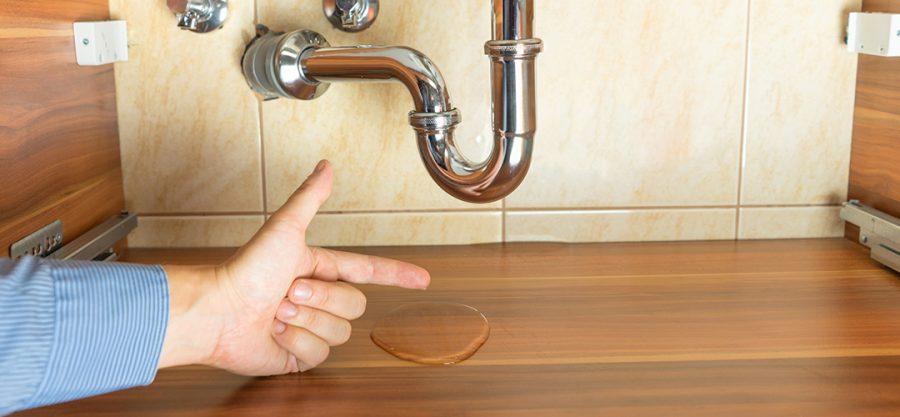 plumbing inspection occurring beneath kitchen sink